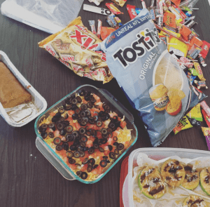office food spread including candy, chips, dip, and other snack